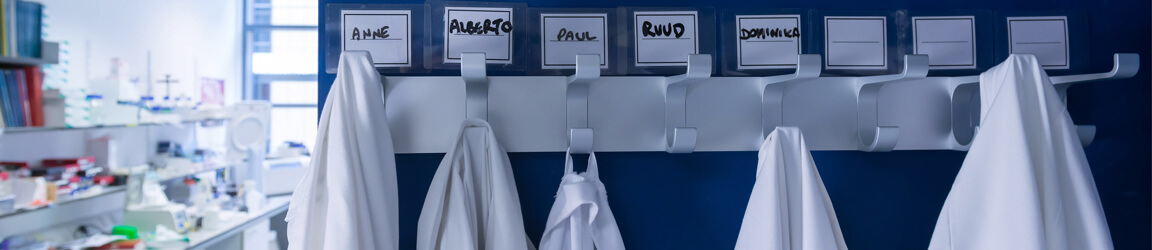 Lab coats hanging under name cards