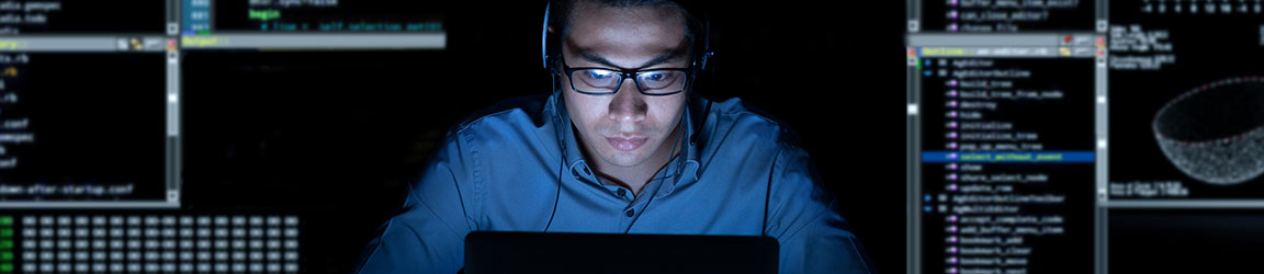 Man with headphones on computer coding