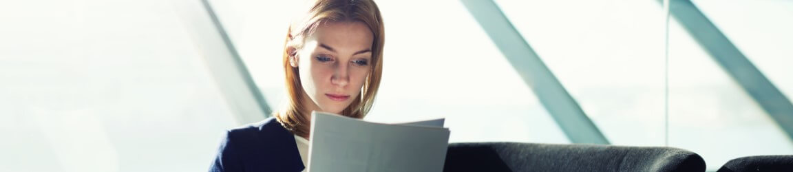 Young woman sitting reading a document | Aerotek.com