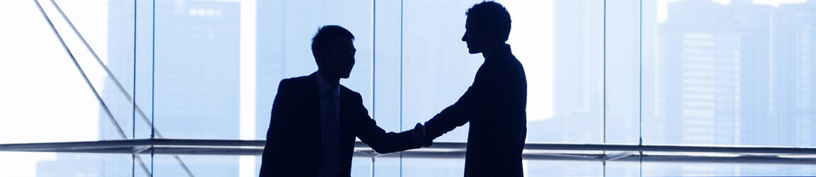 Silhouette of business men shaking hands with a cityscape in the background
