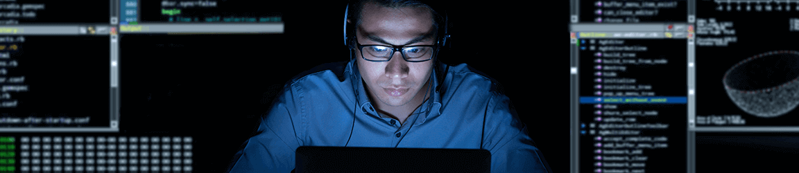 Software engineer working on laptop in the dark