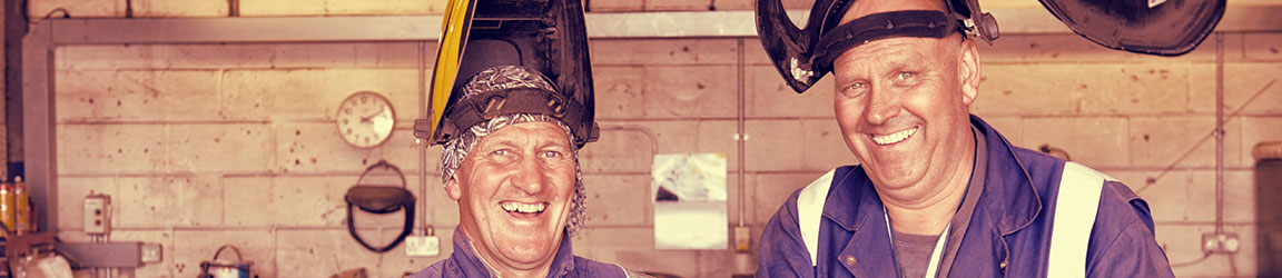 Two welders smiling