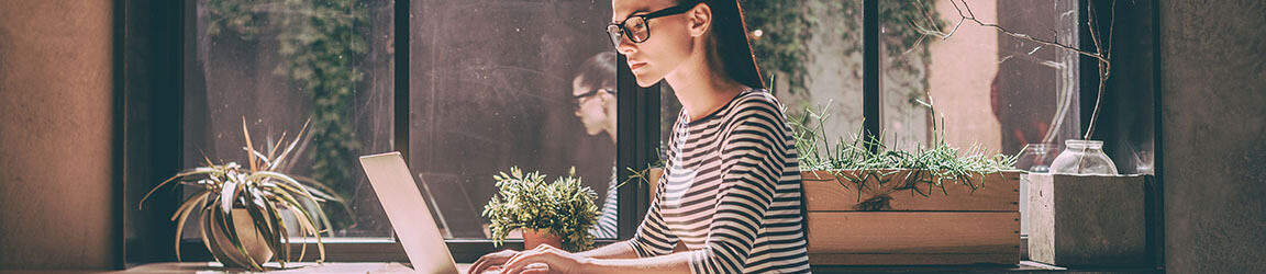 Woman using laptop in a bright office space with plants