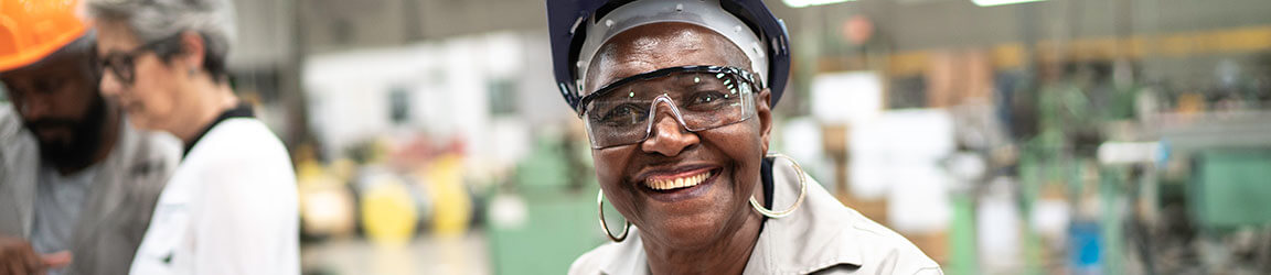 African American woman in manufacturing smiling at camera