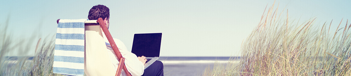 Business man sitting on lounge chair while using laptop on the beach